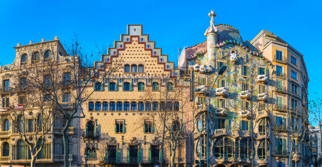 The ornate facade and sinuous curves of Gaudi's iconic Casa Batllo on the Passeig de Gracia illuminated by the warm sunlight of daybreak below blue Mediterranean skies, Barcelona, Spain. ProPhoto RGB profile for maximum color fidelity and gamut.'
